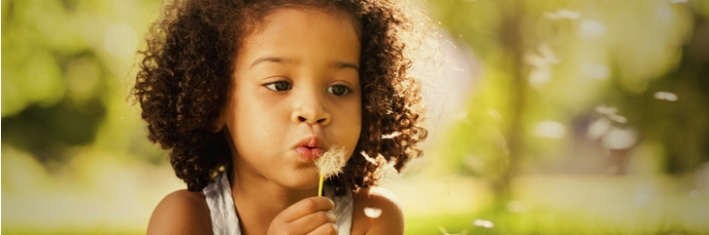 <p>Girl blowing a dandelion</p>